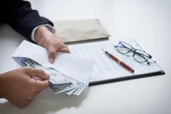 Bribery and corruption concept, bribe in the form of dollar bill. S, Businessman giving money in the envelope while making deal to agreement a real estate Royalty Free Stock Photos