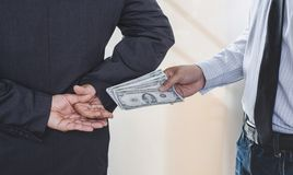 Bribery and corruption concept, bribe in the form of dollar bills, Businessman giving money while making deal to agreement stock images