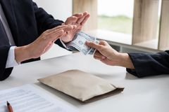 Bribery and corruption concept, senior businessman manager refus. Ing receive money in the envelope to agreement contract, A bribe in the form of dollar bills Stock Photo