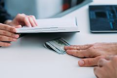 Bribery corruption office illegal business offer. Anti corruption concept. Lady accepting illegal business offer. Bribery at office. Hidden payment in dollars royalty free stock photography