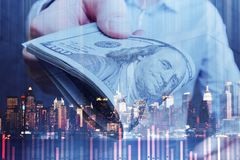 Bribery and crime concept. Businessman handing dollar banknotes on abstract night city background with business chart bars. Bribery and crime concept. Double stock image