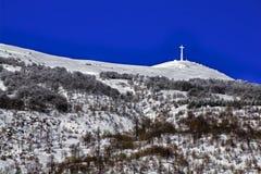 Bric Mindino and monumental cross under the snow. stock image