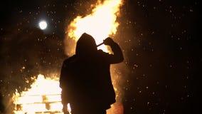 Bricht destruktiver Verhaltenkerl der Revolution auf dem Auto mit einem Baseballschläger Glas Im Hintergrund ist ein Feuer schieß stock video