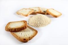 Briciole di pane con i biscotti su bianco Immagini Stock