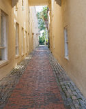 Brick Alley Between Yellow Stucco Walls Stock Images