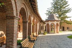 Brick arcades, wood benches in exterior court of Plumbuita Monastery, Bucharest, Romania Royalty Free Stock Photos