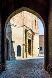 Brick Arch in Saludecio, With Church, Italy. Brick arch, secondary entrance of Saludecio, a little medieval town in the Montefeltro, in the Emilia Romagna region Royalty Free Stock Photography