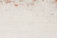 Brick background, old brick wall painted white and with fallen off plaster.  royalty free stock image