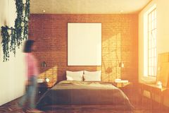 Brick bedroom, poster toned. Brick bedroom interior with a wooden floor, a large window, a gray bed and two bedside tables. A cabinet with mirrors. A woman. 3d Stock Photos