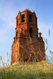 Brick bell tower. Behind grassy foreground Stock Images