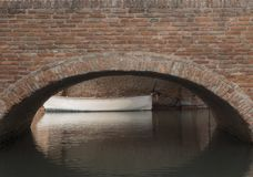 Brick bridge in sight and its arch reflecting on the underlying. Canal of Comacchio, Italy. Small white boat moored just behind the bridge Royalty Free Stock Images