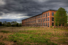 Brick Building Abandoned. A brick building stands abandoned in a field Stock Photo