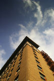 Brick building from below. Photo of brick building from below with blue sky and white clouds creating a vortex Stock Photos