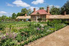 Mount Vernon Greenhouse Washington. The brick building with chimneys of the greenhouse in Mount Vernon, Virginia and the garden with blooming flowers Royalty Free Stock Photography