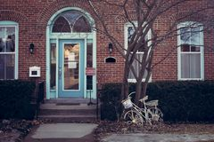 Brick Building with Old Fashioned Bike Against Tree. A brick building in Decorah, Iowa with an arched doorway and long windows. There is an old fashioned bicycle royalty free stock image