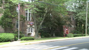 Brick building with sign out front. A view or scene from around town stock video footage