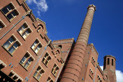 Brick building and tower. The brick built Beurs van Berlage building and chimney tower in Amsterdam, against a clear, blue sky with fluffy, white clouds stock images