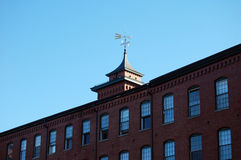 Brick building with wind vane. Royalty Free Stock Photo
