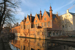 Brick Buildings Along Canal in Brugges, Belgium. Brick buildings with reflection in canal at sunrise in Brugges, Belgium Royalty Free Stock Photos