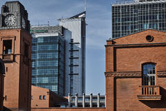 Brick buildings in an old brewery and the facade of a modern office building Stock Photos