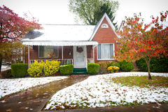 Brick Bungalow. Small brick bungalow style Northern American home with snow on the lawn in autumn Stock Images