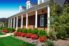 Brick Cape Cod Style Home in the Springtime. Brick cape cod style home with a large front porch in the springtime Stock Image