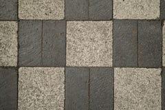 Brick Checkerboard Sidewalk. Weathered dark and light gray brick sidewalk in a checkerboard pattern Stock Photo