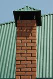 Brick chimney. Chimney made of bricks on a green metal covered roof Stock Images