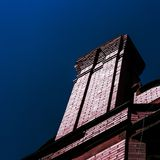 Brick chimney against the blue sky stock photography