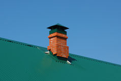 Brick chimney at the green metal roof Stock Photo