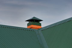 Brick chimney on the green metal roof Royalty Free Stock Photo