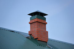 Brick chimney on the green metal roof Stock Photos