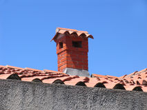 Brick chimney on the house with a tiled roof Royalty Free Stock Photography