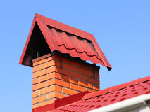 Brick chimney on a red tiled roof taken closeup against of blue Royalty Free Stock Photography