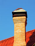 Brick chimney on a red tiled roof taken closeup. Royalty Free Stock Photos