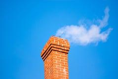 Brick chimney releasing smoke on sky. Stock Photo