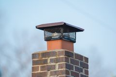 Brick chimney with rodent and pest fencing guard around vent stock images