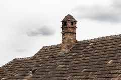Brick chimney on the roof of old house. royalty free stock photography