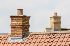 Brick chimney stack on modern contemporary house roof top. Urban housing estate tiled roof in close-up stock photography
