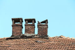 Brick chimney on tile roof of an old wooden house Royalty Free Stock Photo