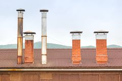 Brick chimneys and tin ventilation pipes on the roof of a wooden hut on a background of green hills on a cloudy day royalty free stock image