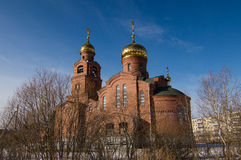 Brick Church with gold domes in the spring Stock Photo