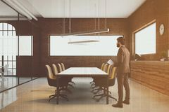 Brick conference room interior, man. Brick meeting room interior with a glass wall and a long table with beige chairs. Ceiling lamps. A businessman. A side view Royalty Free Stock Image