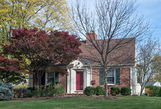 Brick Cottage with Red Maple Tree Royalty Free Stock Images