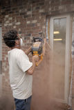 Brick Cutter. Creates a cloud of dust as he cuts a wall opening with a brick saw Stock Photo