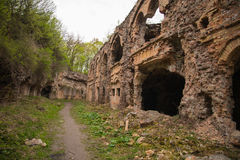 Brick destroyed wall against cloudy sky. Remains of building. Ruins of old fort Tarakanovskiy. Stock Images