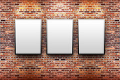 Brick Display Art Gallery with Frames. Three blank, white canvas frames are hanging on a brick wall. Light is shining down on them Stock Image