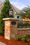 Brick Entrance Post. Multi-colored brick post and fence to entrance of new home - with light fixture Royalty Free Stock Photography
