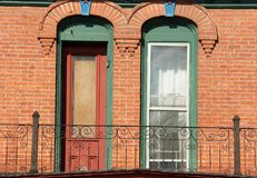 Brick Facade of old Home with Antique Windows. Two narrow and long unique windows on home with brick façade royalty free stock image