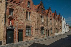 Brick facade of old houses with a blue sunny sky in an empty street of Bruges. With many canals and old buildings, this graceful town is a World Heritage Site Royalty Free Stock Photography